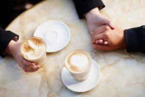 Deux mains et deux cafés sur une table.