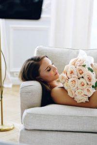 femme allongée sur un canapé avec un bouquet de roses à la main