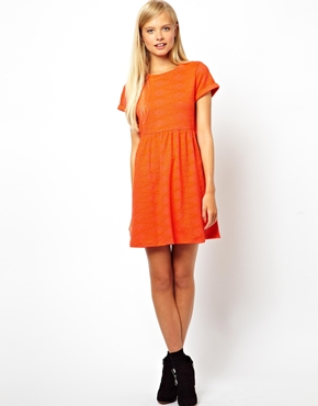 femme blonde debout portant une robe orange