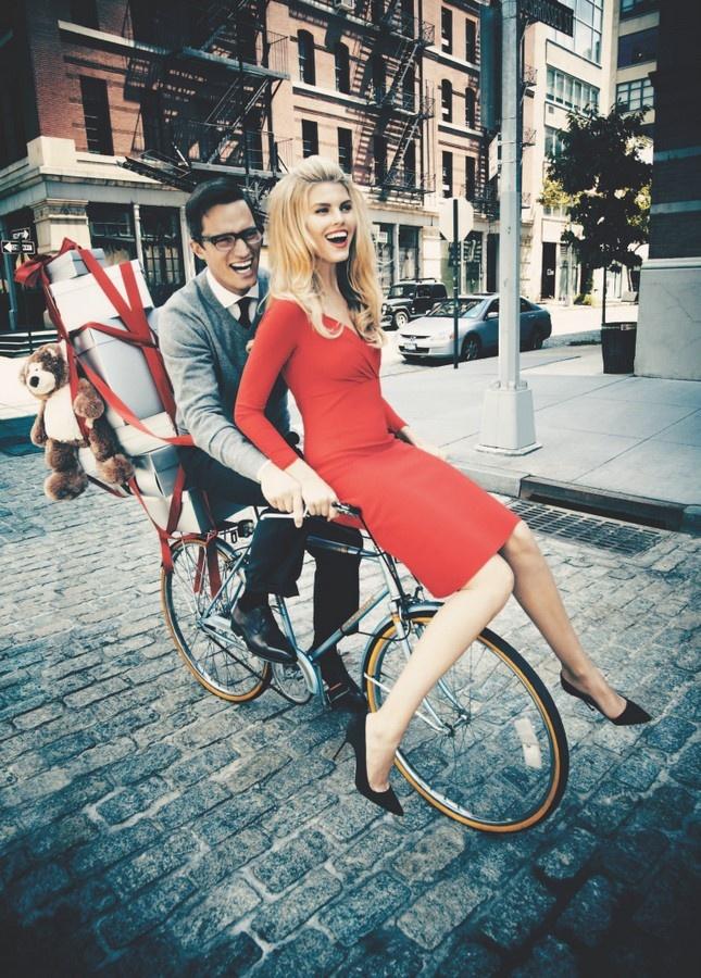 homme brun sur un vélo avec une femme blonde en robe rouge sur son guidon