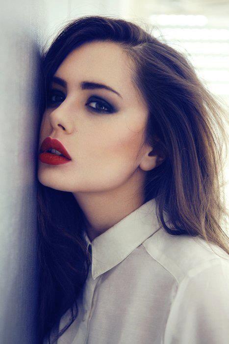 visage d'une femme brune avec un rouge à lèvres rouge