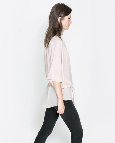 femme debout avec une chemise blanche et un pantalon noir
