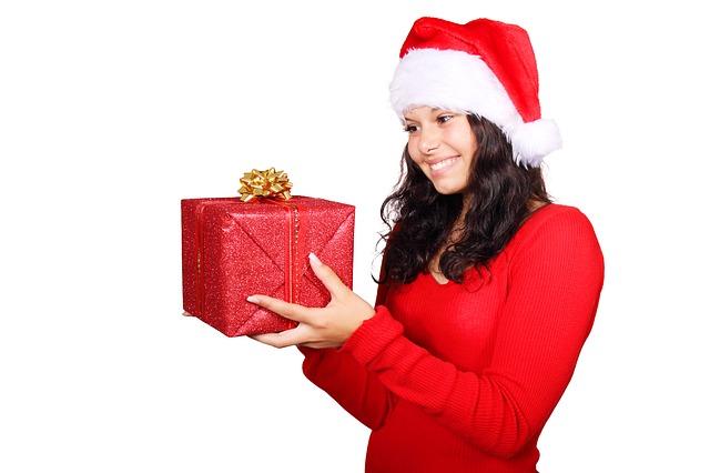Femme habillée en mère noël portant un cadeau dans la main