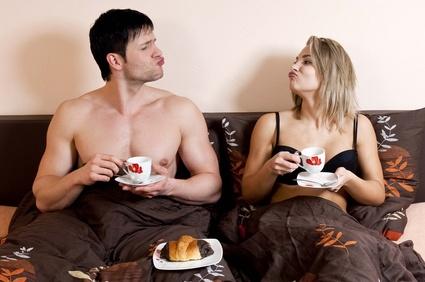 Un homme brun torse nu et une femme brune en soutien gorge noir assis dans un lit. Ils se font des grimaces et prennent leur petit déjeuner ensemble au lit.