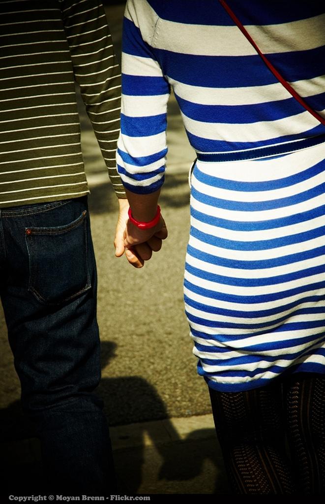 Un homme et une femme de dos qui se tiennent la main.