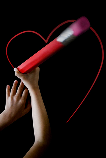 Main qui dessine un coeur en rose sur un fond noir.